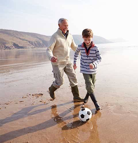 grandfather and grandson playing football on the beach